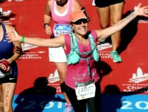Past team member Lucille holds arms out in victory after completing Chicago Marathon