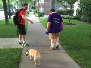 2 members of CLO walk a dog together.