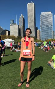 Elizabeth poses in front of Chicago skyline in orange tank top with her medal after Chicago Marathon