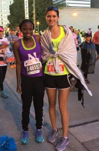 Elizabeth stands with another woman post-marathon in a heat sheet and running gear, demonstrating finding community.