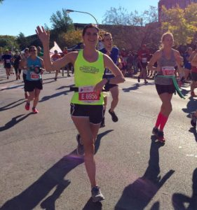Elizabeth runs in the Chicago Marathon in a bright yellow tank top, waving at supporters near the Charity Mile