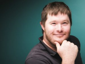 Participant award winner Matthew LaChapelle poses for portrait with hand on chin in front of teal background.