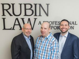 Photo of Rubin Law employees, specializing in creating a special needs trust. 3 men in front of Rubin Law logo