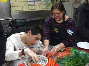 Volunteer supports participant in volunteer activity