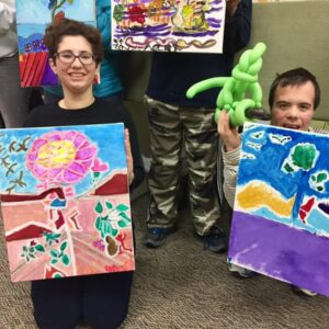 Two participants pose with artwork made in Art Club, an activity that could expand to Highland Park after meet and greet.