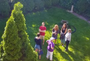 Aerial view of Backyard BBQ attendees chatting outside near a tree.
