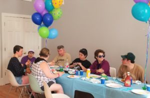 Group chats at first Backyard BBQ, surrounded by colorful balloons to celebrate.