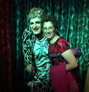 Participant poses with Granny at Hamburger Mary's charity night HamBingo in front of a curtain with a brocade design.