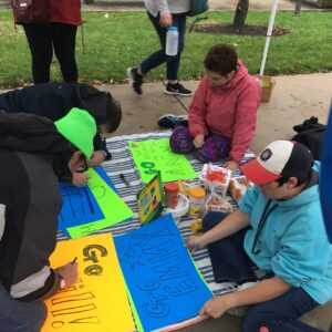 Participants make signs in support of Chicago Marathon team runners