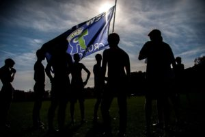 New Trier Cross Country team holds up New Trier flag