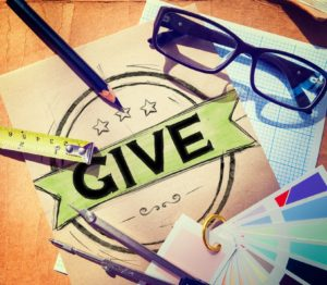 "Bold word ""Give"" centered in photo near glasses and pencils."