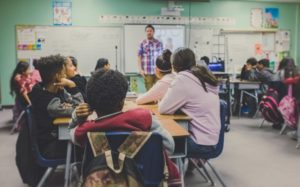 A teacher in front of their classroom, photographed from the students' perspective.