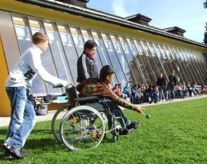 Educators can teach self-advocacy skills to students in a variety of ways. This image shows an individual in a wheelchair with two others on a grassy lawn.