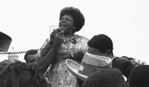 Fannie Lou Hamer with a microphone speaking to a crowd.