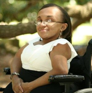 Vilissa Thompson in a white and black dress with her wheelchair.