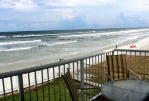 Florida house view over the ocean with deck railing in frame