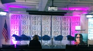 Stage at 1871 Chicago event with six blue chairs and purple lights highlighting 1871 logos behind stage.