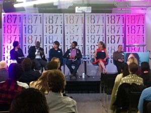 Panelists listen to each other speak on inclusive technology in Chicago on stage at 1871.