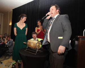 Preparing for the Golden Ticket raffle drawing. A woman in green stands on the left, next to the golden raffle drum and a woman in red. A man in a gray suit speaks into a microphone as another man pulls the winning ticket.