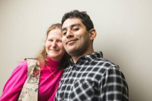 Jenny, in pink, stands with her boyfriend Nestor, who wears a black and white flannel shirt.