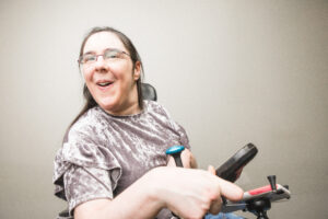 Sarah smiles during a photoshoot wearing a lavender shirt and using her wheelchair.