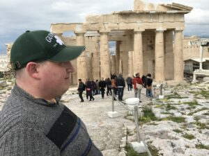 "Jonathan stands in front of ancient ruins in Greece as part of his ""Create Your Journey"" trip"