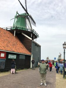 Jonathan stands to the right of a green windmill in Amsterdam