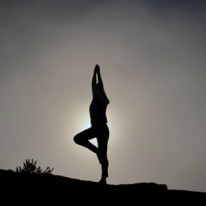 A silhouetted person performs a yoga pose in front of a grayscale background.
