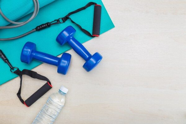 Blue dumb bells, a water bottle, and other assorted exercise class equipment lays on a cream colored floor.