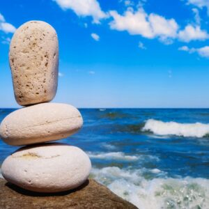 three balancing rocks in the foreground and an ocean view with blue skies and clouds in the background