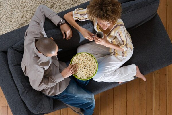 2 people sit on a couch with popcorn between them.