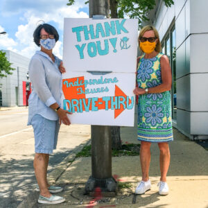 "Ann & Niki hold a sign saying ""Thank You Independent Futures Drive-Thru"" while wearing masks"