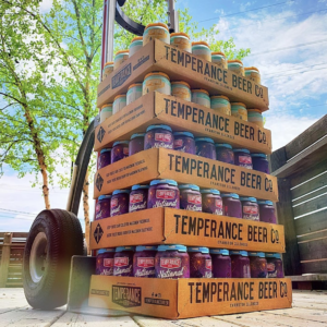 Cases of Temperance Beer stacked on top of each other with a beautiful summer sky in the background.