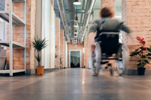 A person in a wheelchair moves down a hallway in action